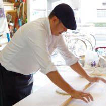 講師がこねた蕎麦粉を棒を使って伸ばす方法を実演する