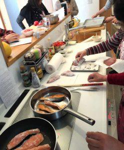 IHキッチンを使って鮭のムニエルを料理する様子
