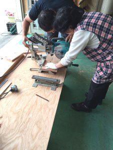 女性が電動のこぎりを使って木を切る