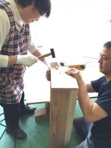 参加者の女性が金槌を使って箱に釘を打つ