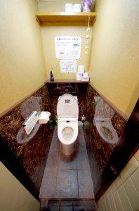 リフォーム後のトイレ。洋式のトイレとなっており、ウォッシュレットも完備。壁も高級感がある。