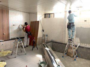 お風呂に入った人が落ち着いてリラックスできるよう、シックな色の化粧板をタイルの上から貼っている。