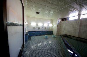 リフォーム前の大浴場の全景。全体的に清掃は行き届いているが、タイルをみると古い感じがする。