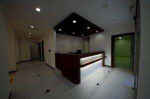 眼科の受付。間接照明による落ち着いたモダンな空間で、病院らしさを感じさせない。