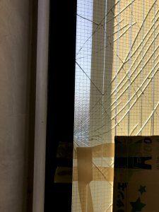 窓ガラスが割れ、割れた部分をガムテープとダンボールで補強している