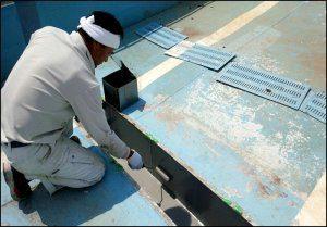 塗料をローラーで側溝に塗ります