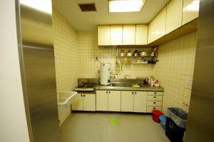 リフォーム前の給湯室。給湯器やガスコンロが設置されており、壁は昔ながらのタイル張り。