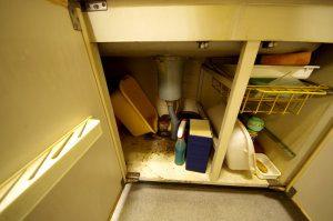シンクの収納スペース。様々な器具が雑然と収納されている。