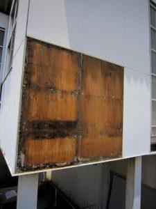 壁を剥がしたところ。裏のベニヤ版が露出している。